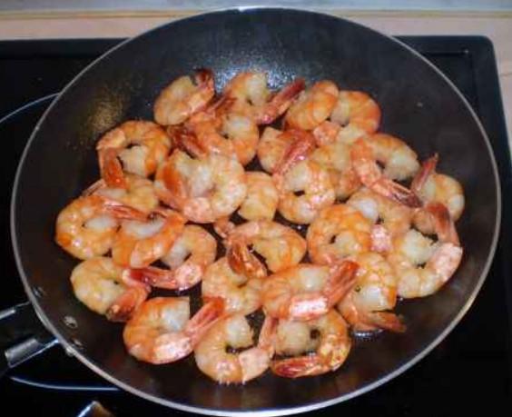 1. Этап. В сковороде на среднем огне разогрейте оливковое масло. Добавьте креветки и обжарьте до полной готовности. Дайте остыть, затем нарежьте небольшими кусочками.