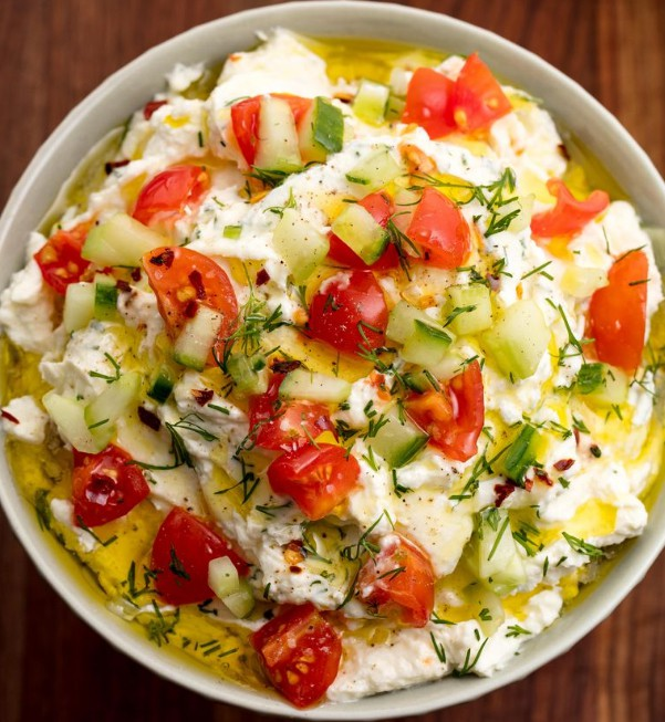 1. Stage. Transfer dip to a serving bowl and top with cucumber, tomatoes, dill, and a drizzle of oil.