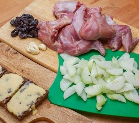 1. Этап. Кролика нарежьте на порционные кусочки, лук нарежьте полукольцами, у чернослива удалите косточки, хорошо промойте и нарежьте кусочками, чеснок измельчите ножом. У хлеба удалите корку и смажьте медом с горчицей.