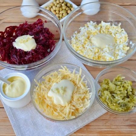 1. Этап. Свеклу очистите и натрите на крупной терке, добавьте к ней два зубка чеснока пропущенных через пресс и майонез, перемешайте. Сыр натрите так же на крупной терке смешайте его с майонезом и одним зубком чеснока. Яйца очистите от скорлупы, натрите на терке, добавьте немного соли и майонез. Огурцы так же натрите на терке и немного отожмите лишнюю жидкость.