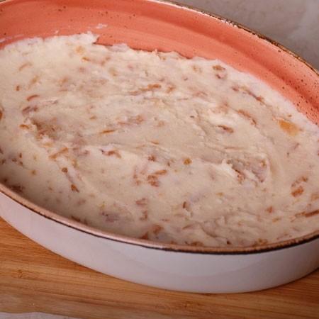 1. Этап. Форму для запекания смажьте немного маслом, выложите на дно половину картофельного пюре и разровняйте.
