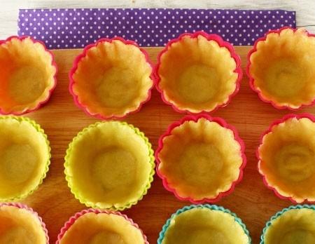 1. Этап. Тесто достаньте из холодильника, разделите на 12 ровных частей и раскатайте по размеру силиконовых формочек для кексов. Выложите в них тесто и хорошо придавите, поставьте в холодильник еще на 20 минут что бы во время выпечки корзинки не потеряли свою форму. Затем выпекайте корзинки в предварительно разогретой духовке до 180 градусов 5-15 минут.
