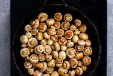 1. Этап. Шампиньоны промойте и обсушите. На сковороде разогрейте половину масла и выложите грибы, готовьте около 5 минут периодически помешивая, грибочки должны слегка подрумяниться.