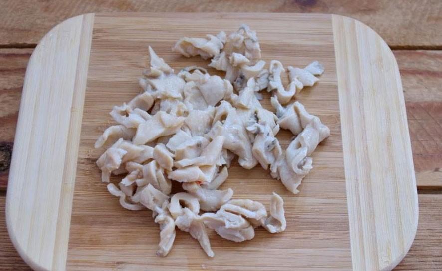 1. Етап. Кальмари добре відіжміть від рідини і також наріжте на шматочки.