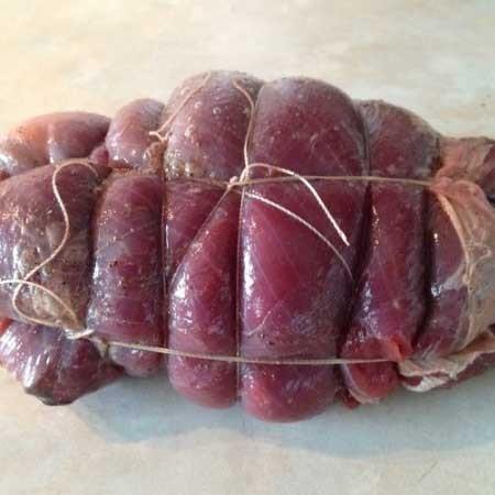 1. Этап. Выложите на верх мяса промытый чернослив без косточек. Сверните рулетом и перевяжите ниткой.