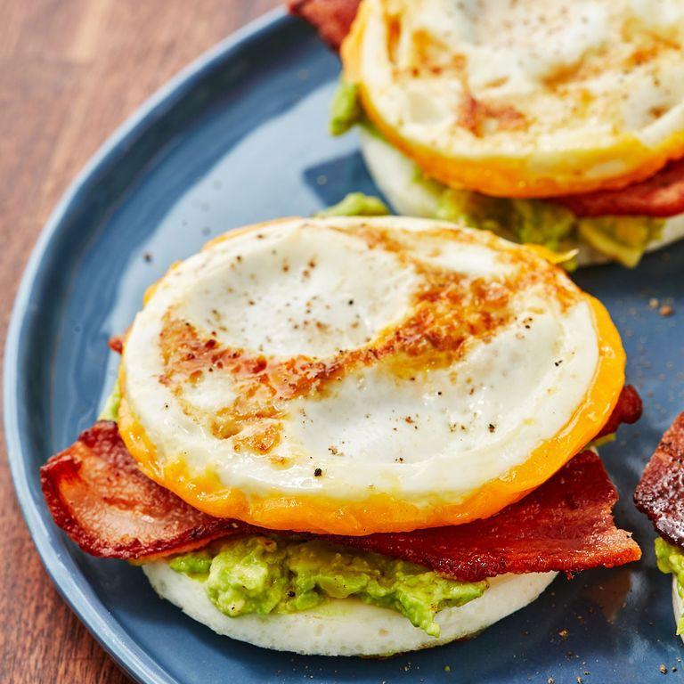 1. Етап. Викладіть яєчну булочку без сиру на тарілку. З авокадо зробіть пюре і викладіть на яйце, а зверху приготовлений бекон. Накрийте все другим яйцем і подавайте.