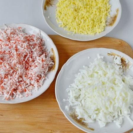 1. Этап. Отварные яйца разделите на белки и желтки, натрите их на мелкой терке по отдельности, крабовые палочки также натрите на мелкой терке.
