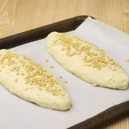 1. Этап. Тесто разделите на две части, сделайте с него лепешку, посыпьте сыром и скатайте в рулет. Затем придайте форму батона, сделайте несколько надрезов, снова посыпьте сыром и орехами. Орехи немного вдавите в хлеб то бы они хорошо держались.