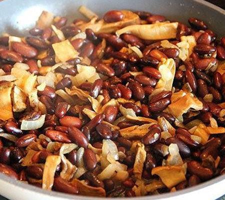 1. Этап. Затем добавьте в сковороду к луку добавьте нарезанные грибы. Когда грибы немного поджарятся добавьте фасоль, посолите и поперчите по вкусу. Влейте немного отвара, накройте крышкой и тушите 15 минут на среднем огне.