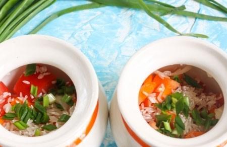 1. Этап. Рис с овощами выложите в горшочки, добавьте по одной чайной ложки растительного масла, нарезанный зеленый лук.