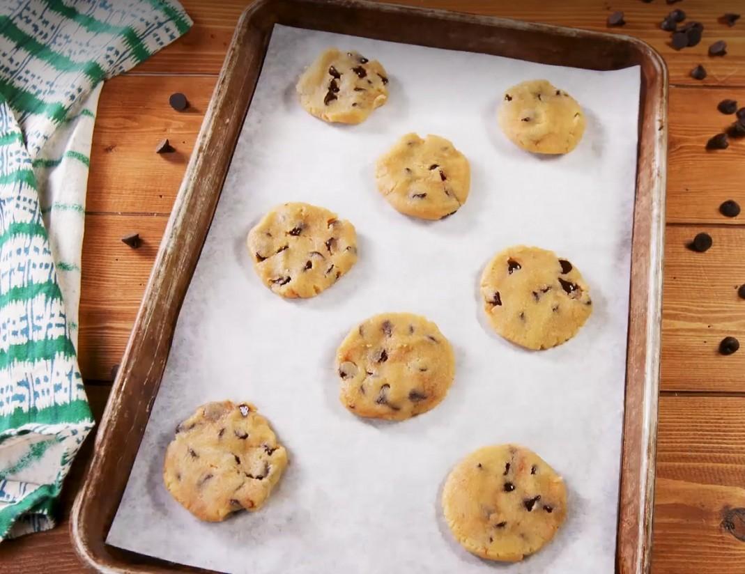 1. Этап. Добавьте шоколадные капли в тесто для печенья. Сформируйте тесто в шарики размером 2-3 см и разложите на расстоянии друг от друга на протвине, выстланном пергаментом. Прижмите шарики дном стакана, слегка смазанным кулинарным спреем.