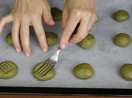 1. Этап. Разделите тесто на небольшие шарики, а что бы тесто не прилипало к рукам смочите их в холодной воде. Выложите шарики теста на протвинь, немного придавите руками и можете сделать рисунок вилкой.
