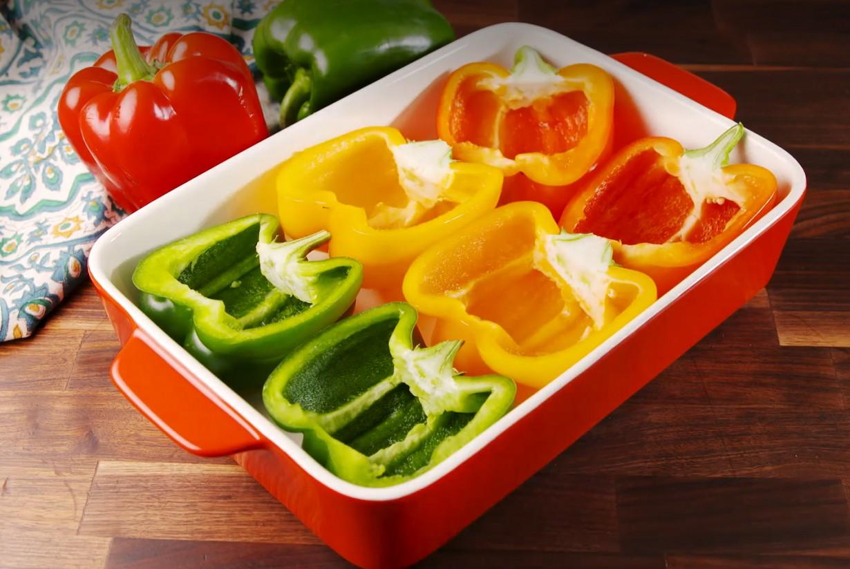 1. Этап. Разогрейте духовку до 200 С. Выложите перец разрезанный пополам в большую форму для запекания. Добавьте в блюдо немного воды и запекайте перец 5 минут.