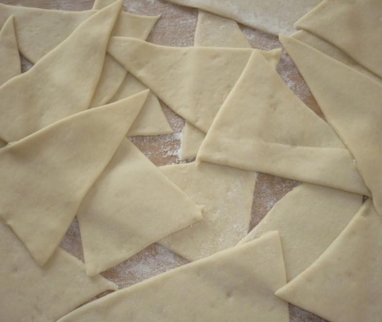 1. Этап. Поместите тесто между двумя листами пергаментной бумаги и раскатайте в прямоугольник толщиной 0,3 см. Ножом или ножом для пиццы нарежьте тесто на треугольники.