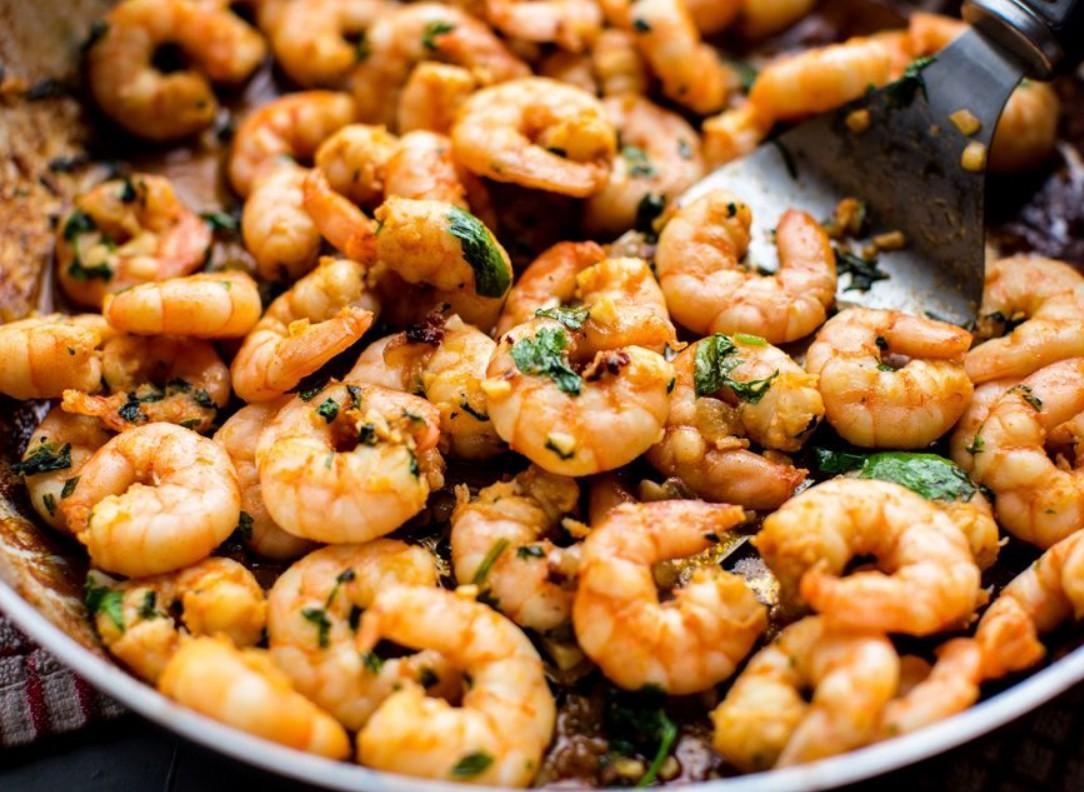 1. Этап. В сковороде на среднем огне разогрейте оставшуюся столовую ложку оливкового масла. Добавьте мелко нарезанный лук и готовьте 2 минуты. Добавьте креветки и готовьте до розового цвета около 2-5 минут.