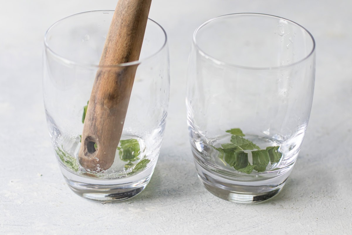 1. Stage. Using a muddler (or handle of a wooden spoon) crush the mint leaves with the sugar and lime juice. Add ice to each glass.