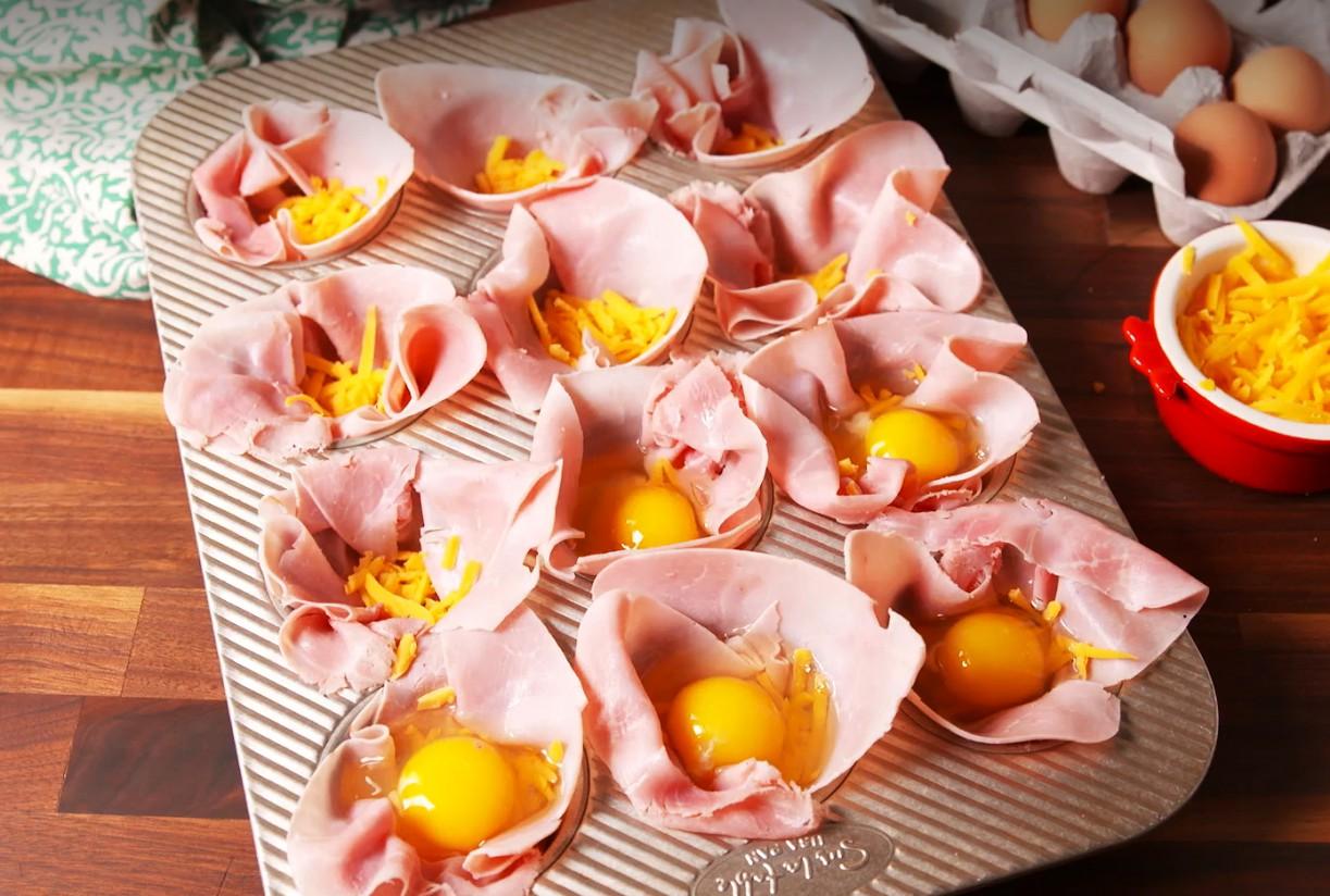 1. Этап. Разогрейте духовку до 200º и смажьте форму для маффинов на 12 шт маслом. Выложите каждую чашку ломтиком ветчины и посыпьте натертым чеддером. В каждую чашку ветчины разбить по яйцу и приправить солью и перцем.