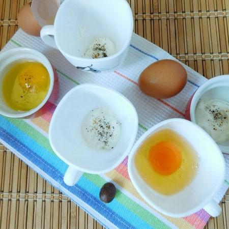 1. Этап. Яйца кокот очень удобно готовить в чашках. На дно чашек положите по 1 ст. л. сметаны, посолите и поперчите сверху по вкусу и вбейте аккуратно по яйцу.