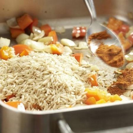 1. Этап. На этой же сковороде где готовилась курица обжарьте в течении 3 минут перец, лук и нарезанный чеснок. Затем добавьте паприку и рис, немного обжарьте.