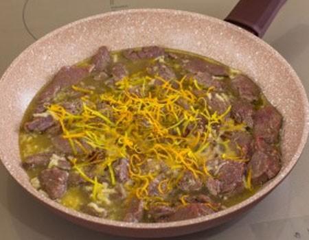 1. Этап. Мясо переложите в немного смазанную маслом сковороду вместе с маринадом, добавьте цедру и тушите 30-40 минут на медленном огне под крышкой, в конце посолите и поперчите по вкусу.