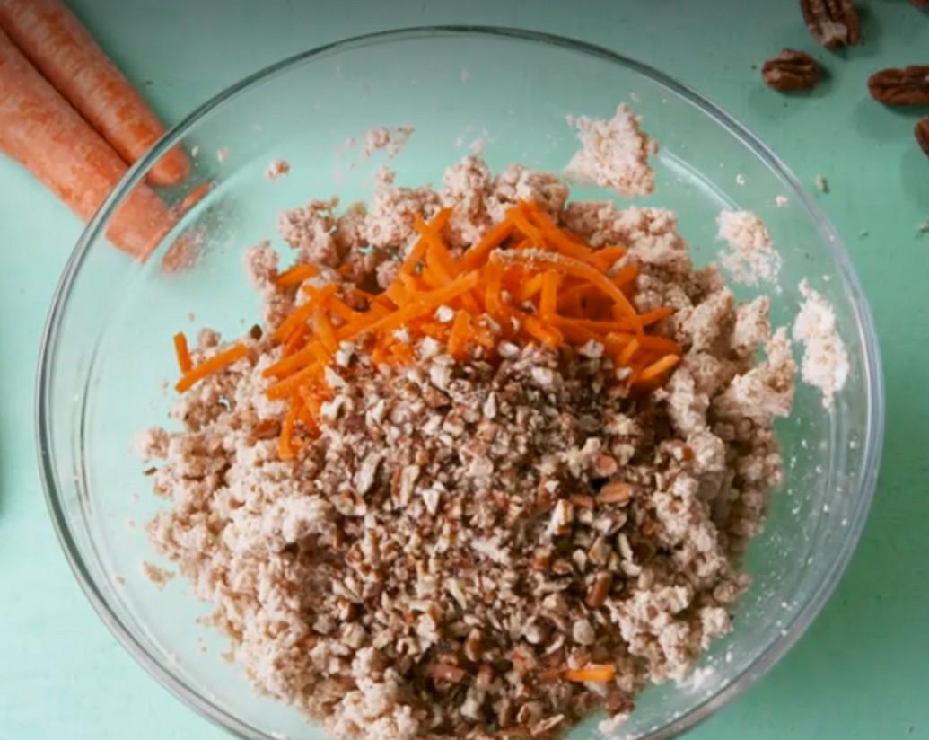 1. Этап. Морковь натрите на мелкой терке. Орехи нарежьте ножом. В большой миске с помощью ручного миксера взбейте сливочный сыр, кокосовую муку, стевию, ваниль, корицу и мускатный орех. Добавьте морковь и орехи пекан.