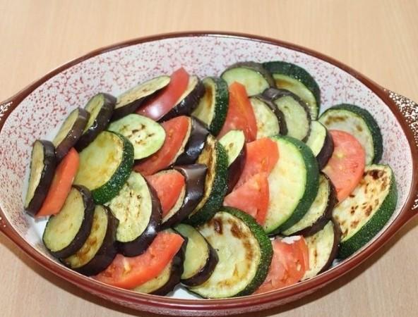 1. Этап. Помидоры нарежьте кружочками. Овощи переложите в глубокую форму для запекания чередуя их.