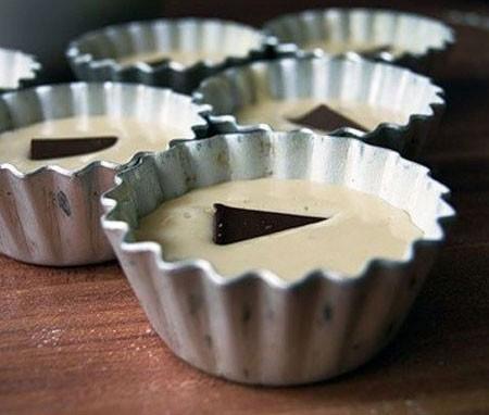 1. Этап. Выложите тесто в смазанные маслом и посыпанные мукой формочки, заполняя их примерно на 2/3. В центр каждой формочки положите по кусочку шоколада.