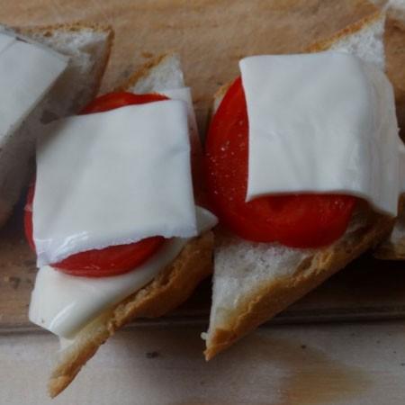 1. Этап. Выложите на моцареллу, помидор, посолите и поперчите, выложите листья базилика и закройте вторым куском хлеба.