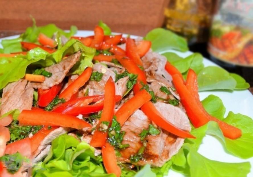 1. Этап. На тарелку уложите листья салата, чередую выложите мясо, сладкий перец и зелень с чесноком. Полейте приготовленным соусом и украсьте кунжутом.