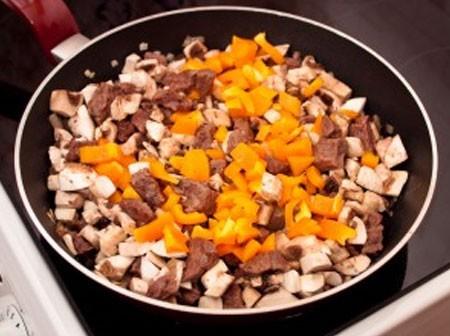 1. Этап. Добавьте в сковороду грибы и перец, посолите, поперчите по вкусу и готовьте около 5-10 минут.