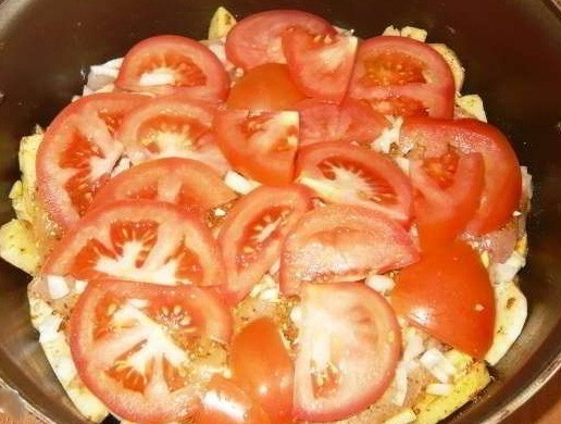 1. Этап. Лук нарежьте кольцами, уложите на мясо, затем помидоры нарежьте дольками и выложите следующим слоем.