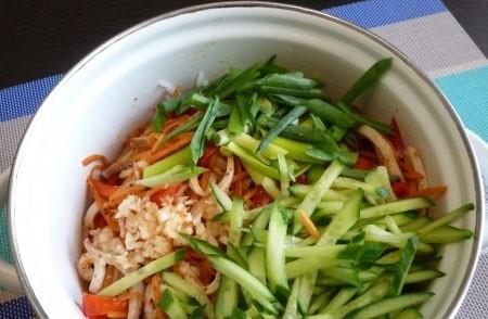 1. Этап. В лапшу добавьте остывшие овощи с кальмаром, огурец, пропущенный через пресс чеснок и нарезанный зеленый лук.