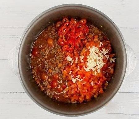 1. Этап. Добавьте нарезанный сладкий и острый перец, измельченный чеснок. Готовьте периодически мешая.