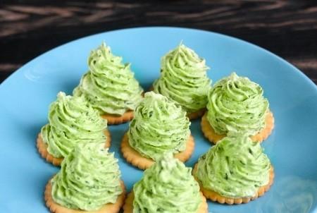 1. Этап. С помощью кондитерского шприца выдавите получившуюся зеленую массу на крекеры в виде ёлочек.