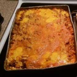 1. Этап. Готовьте лапшу согласно инструкции на упаковке. Поместите в форму для выпечки лапшу, а затем мясо. Затем слой сметаны с томатным соусом, а сверху с сыром.