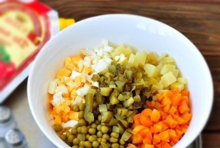 1. Этап. Морковь, картофель и яйца очистите. Нарежьте кубиками, так же добавьте нарезанные огурцы и консервированный горошек.