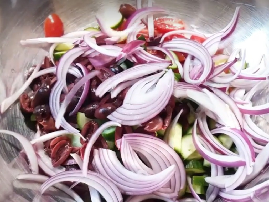 1. Этап. В большой миске смешать помидоры нарезанные пополам, огурцы нарезанные соломкой, оливки разрезанные пополам и красный лук нарезанный перьям. Осторожно разложите фету.