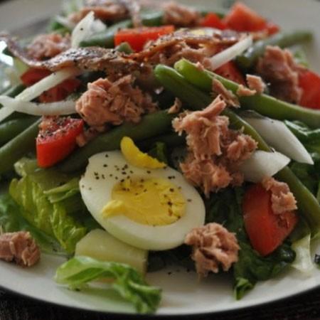1. Этап. На тарелку выложите салат ромен, затем яйца с картофелем, нарезанный соломкой лук, анчоусы, тунец и нарезанные пополам помидоры черри, все посолите, поперчите и полейте майонезом.