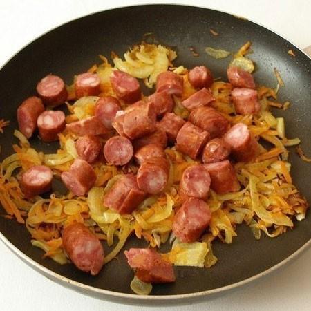 1. Этап. На небольшом количестве растительного масла обжарьте лук с морковью до мягкости, затем добавьте колбаски и готовьте еще 5 минут.