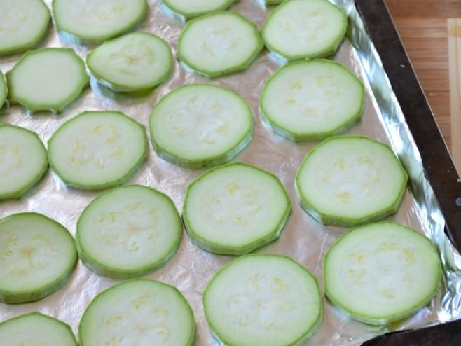 1. Этап. Противень для запекания нужно застелить фольгой, смажьте сверху маслом. Кабачки нарежьте кружочками и переложите на противень.