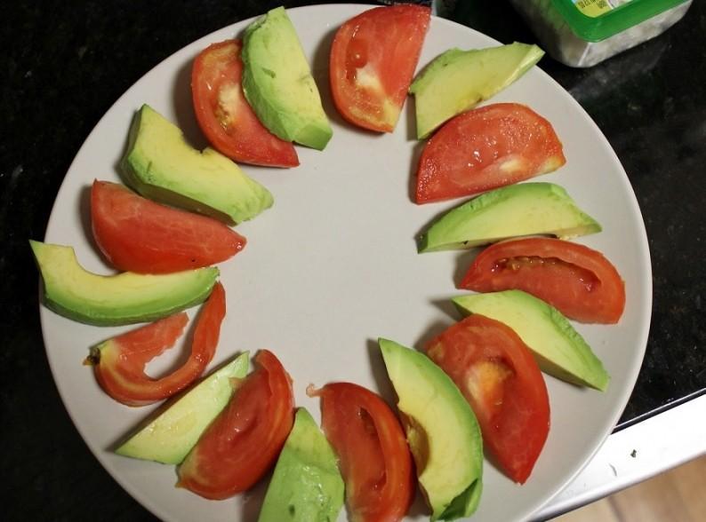 1. Этап. Авокадо очистите, удалите косточку и нарежьте его полосками, помидоры нарежьте дольками. Переложите авокадо и помидоры на плоскую тарелку чередуя их по очереди.