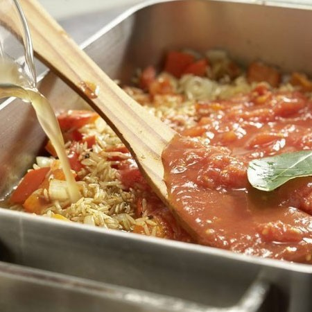 1. Этап. Влейте в сковороду вино, тушите 5 минут. Затем добавьте нарезанные помидоры в собственном соку вместе с соком. и лавровый лист, влейте бульон. Доведите до кипения. Посолите и поперчите по вкусу.