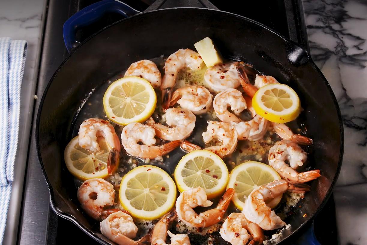 1. Этап. В большой сковороде на среднем огне растопите 1 столовую ложку сливочного и оливкового масла. Добавьте креветки, дольки лимона, измельченный чеснок, перец чили и приправьте солью. Готовьте, периодически помешивая, примерно по 3 минуты с каждой стороны, пока креветки не станут розовыми и непрозрачными.