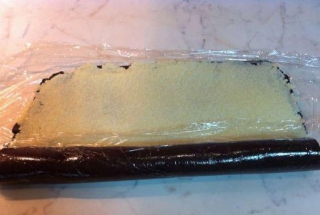 1. Stage. On the table, spread the cling film, put the chocolate mass from the cookies, evenly even out. Put the curd filling and roll it up.