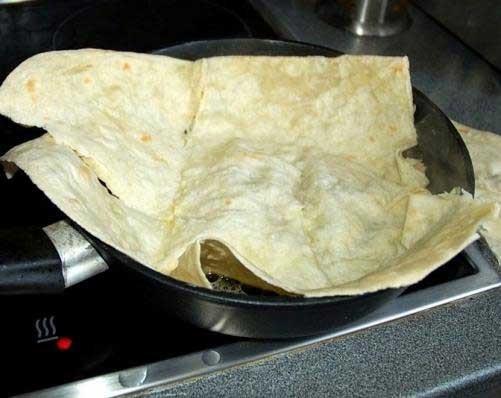 1. Этап. Лаваш хорошо сбрызнуть холодной водой и положить на разогретую с сливочным маслом сковороду так, чтобы края свисали за бортики сковороды зажареной стороной вверх.