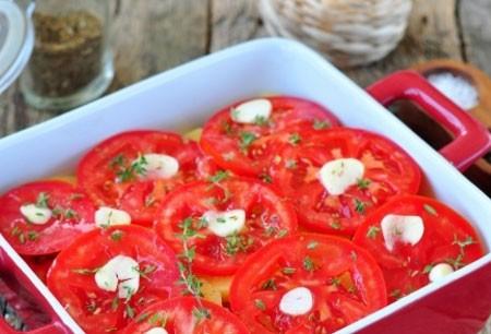 1. Этап. На помидоры выложите тонко нарезанный чеснок. Повторите слой картофеля и помидоров. На верх положите еще чеснок и поставьте в разогретую духовку до 180 градусов, запекайте 35 минут, если будет необходимо накройте форму фольгой.