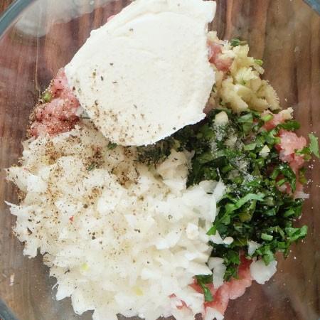 1. Этап. К фаршу добавьте пропущенный через пресс чеснок, творожной сыр, рубленную петрушку, мелко нарезанный лук (или пропущенный на мясорубке), посолите и поперчите по вкусу. Хорошо перемешайте руками.