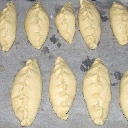 1. Этап. Готовые пирожки переложите на противень застеленный пергаментом и немного смазанный маслом. Дайте постоять в теплом месте 20 минут.