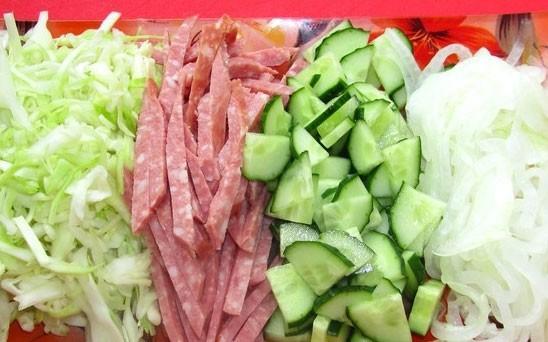 1. Этап. Нашинковать капусту и немного разомните руками что бы была мягкой. Огурец нарежьте пластинками, лук полукольцами, а колбасу соломкой.