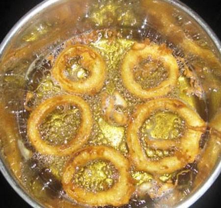 1. Этап. Луковые колечки окуните в кляр и опустите в горячее масло, его должно быть много чтобы колечки полностью были покрыты маслом.